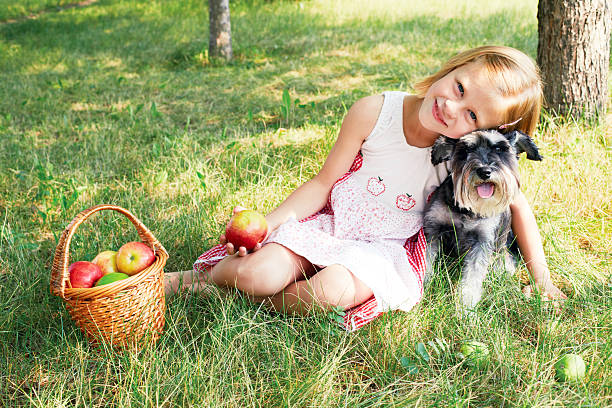 Cute little girl sitting on the grass in the garden stock photo