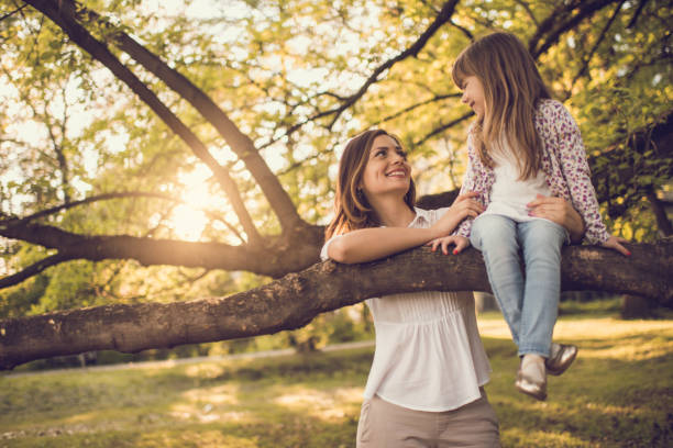 Cute little girl sitting on tree branch and looking at mother stock photo