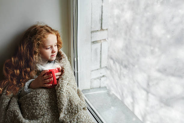 Cute little girl sitting with a cup by the window Cute little girl sitting with a cup of hot cocoa by the window and looking on first falling snow through glass early Christmas morning.  wrapped in a blanket stock pictures, royalty-free photos & images