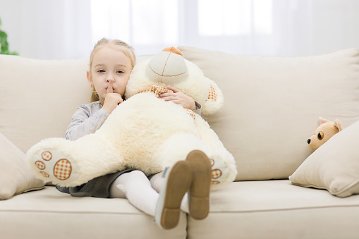 Cute little girl sitting with her legs curled up, teddy bear on her knees. Girl is showing silence sign.