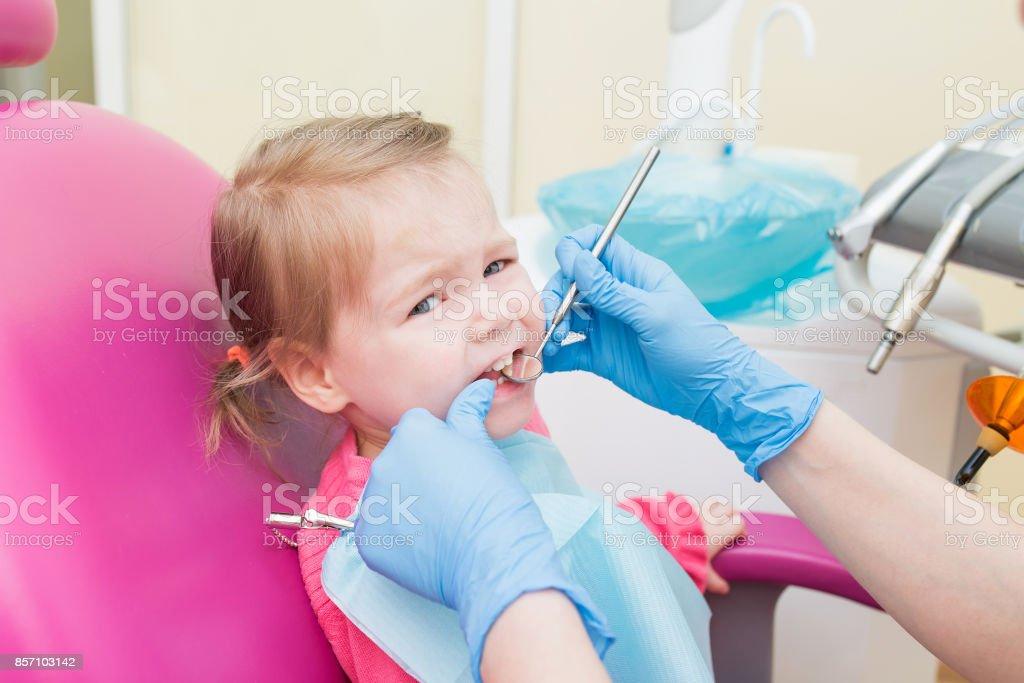 Cute poco niña sitts en silla dental en el consultorio del dentista, closeup retrato - foto de stock