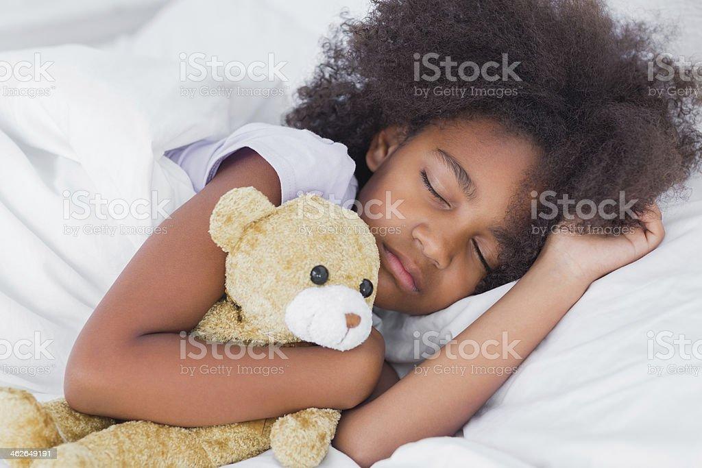 Cute little girl sleeping in bed cuddling teddy bear stock photo