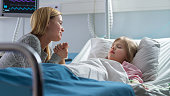 istock Cute Little Girl Sleeps on the Bed in the Children's Hospital, Her Mother Sits Beside, Worrying but Hopeful. Modern Pediatric Ward. 1038799686