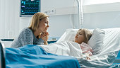 istock Cute Little Girl Sleeps on the Bed in the Children's Hospital, Her Mother Sits Beside, Worrying but Hopeful. Modern Pediatric Ward. 1038799896