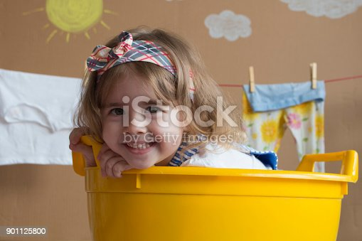 istock cute little girl smiles and sits in a yellow bath 901125800
