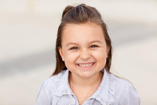 süßes kleines mädchen lächelnd und blick in die kamera - rüschenbluse stock-fotos und bilder