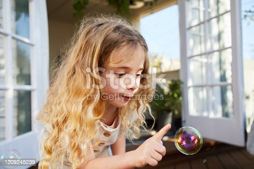Adorable little popping soap bubbles with her finger while playing outside on her backyard patio at home