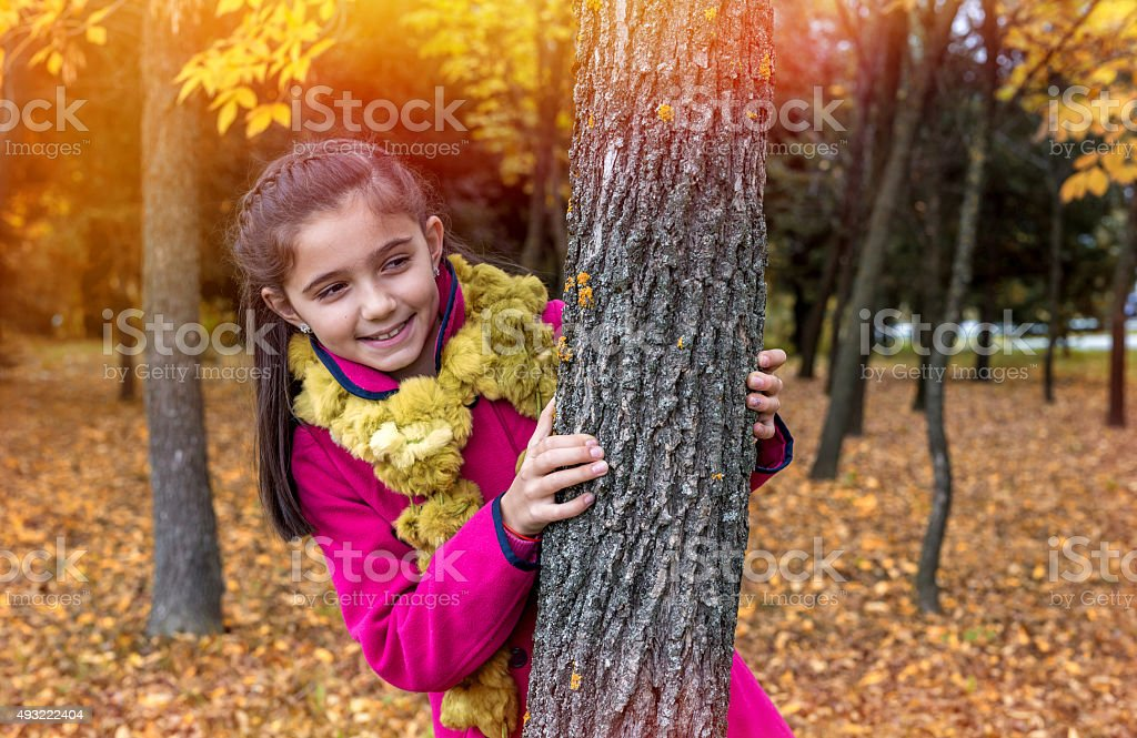 Cute little girl smiling by the tree stock photo