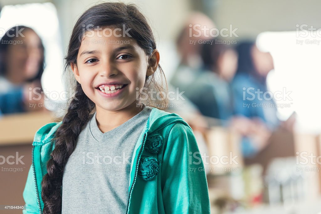 Cute little girl smiling in charity food bank stock photo