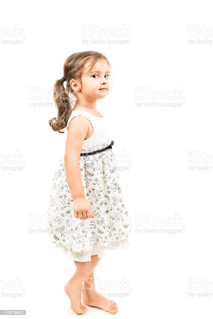 Cute little girl standing barefoot isolated stock photo