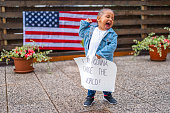 Two years old cute little african-american girl, wearing white t-shirt and jeans jacket, standing in the rain and holding a fist with one hand and a white poster with a handwritten message: I AM GONNA CHANGE THE WORLD! She has mouth opened like she is shouting with a smile on her face and she is looking away. American flag on the wooden fence and flower pots in the blurred background.