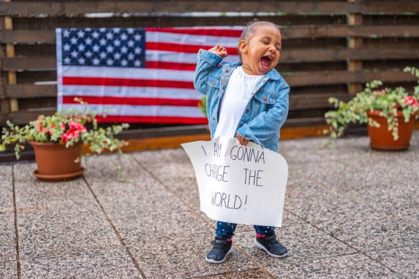 Nettes kleines Mädchen, das im Regen steht und eine Faust und ein Poster mit der Botschaft hält: I AM GONNA CHANGE THE WORLD! – Foto