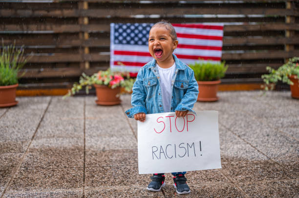 Nettes kleines Mädchen steht im Regen und hält ein Poster mit der Botschaft: Stoppt Rassismus! – Foto