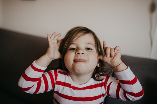 Cute Little Girl Sticking Her Tongue Out Stock Photo