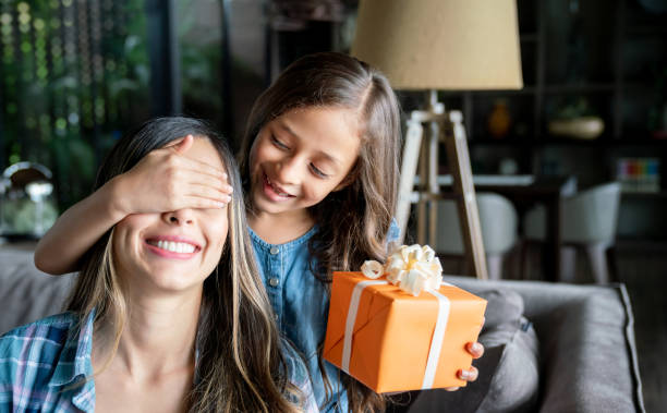 cute little girl surprising her mom with a gift box for mother's day while covering her eyes - mothers day stock pictures, royalty-free photos & images