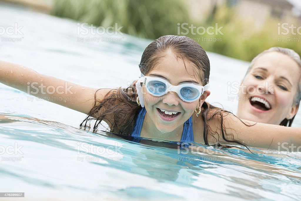 Cute little girl swimming with grandmother, wearing goggles royalty-free stock photo