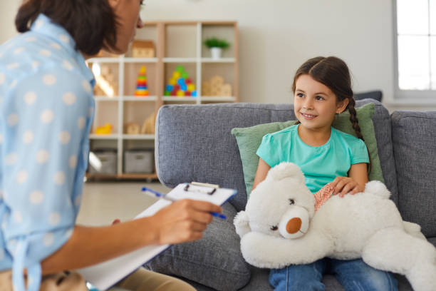 Cute little girl talking to child psychologist during therapy session in cozy modern office stock photo