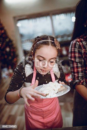 istock Cute Little Girl Tasting her Homemade Cake 898239880