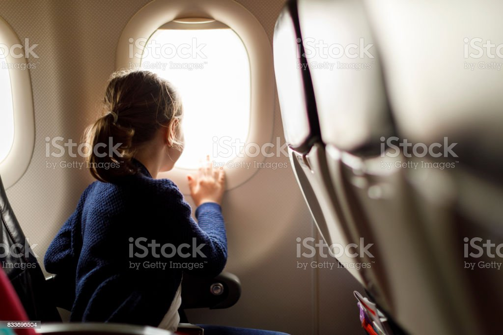 Cute little girl traveling by an airplane stock photo