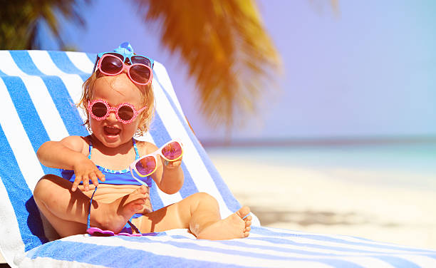 cute little girl trying on sunglasses at beach stock photo