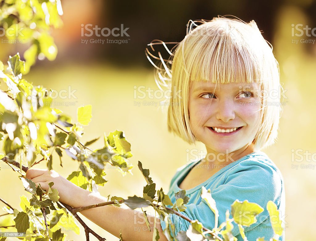 Cute little girl under tree, smiling over her shoulder stock photo