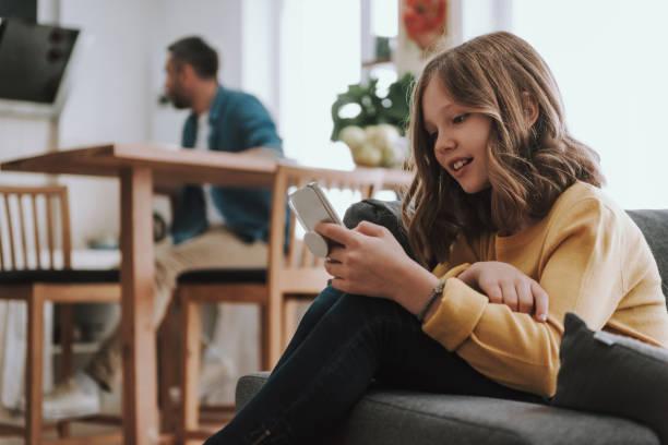 Niedliches kleines Mädchen mit Handy zu Hause – Foto