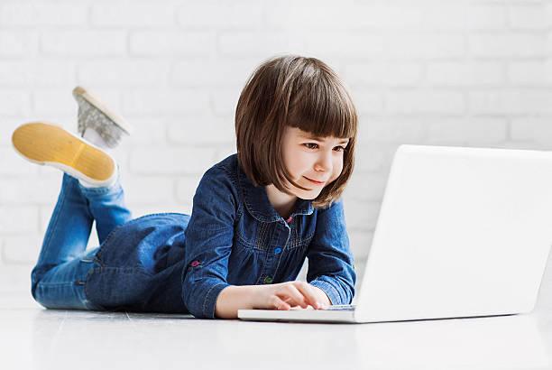 Cute little girl using laptop stock photo