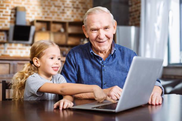 niedliche kleine mädchen mit laptop mit seiner enkelin - kücheneinrichtung nostalgisch stock-fotos und bilder