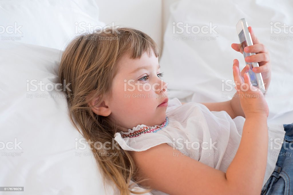Cute Little Girl Using Mobile Phone At Home Stock Photo Download Image Now Istock
