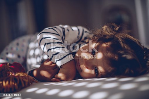 1008826222istockphoto Cute little girl waking up 1063971590