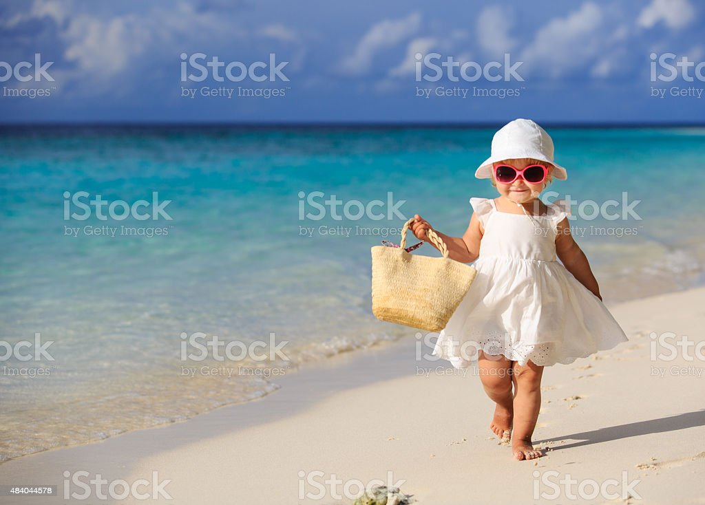cute little girl walking on summer tropical beach stock photo