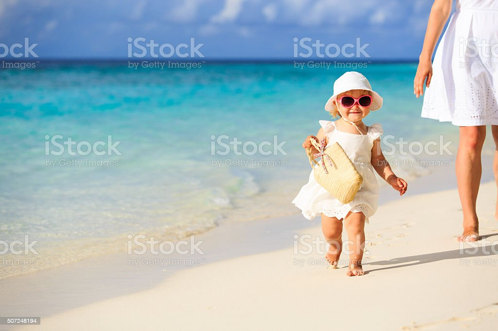 cute little girl walking on the beach with mother stock photo