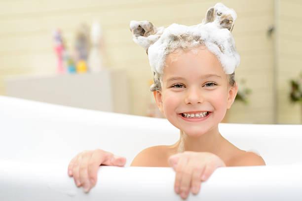 niedliche kleine mädchen ihre haare waschen - kinderbadewanne stock-fotos und bilder