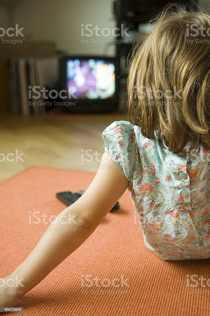 cute little girl watching television. stock photo