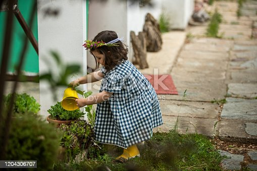 Cute little girl watering plant in back yard