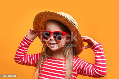 604367022 istock photo Cute little girl wearing a hat and sunglasses on yellow background 1201627366