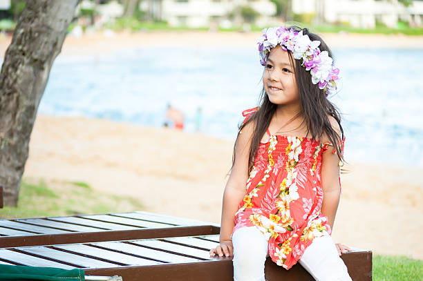 cute little girl wearing a lei on a hawaiian beach - hawaiian ethnicity stock photos and pictures