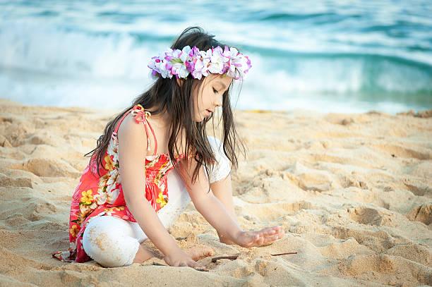 Cute little girl wearing a lei plays on Hawaiian beach stock photo