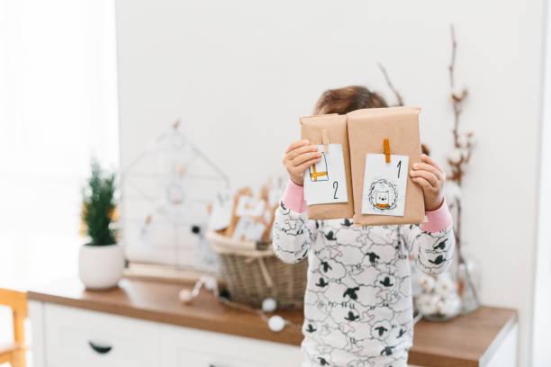 Niedliche kleine Mädchen tragen Pyjamas hält Advent Kalender kleine Geschenke – Foto