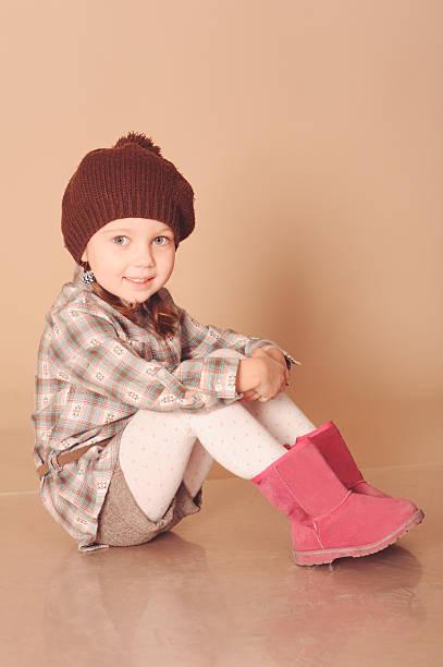 niedliche kleine mädchen in winterkleidung - lammfellstiefel stock-fotos und bilder