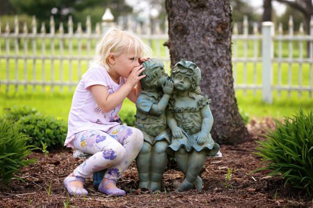 Cute Little Girl Whispering Secret to Little Garden Statue Friends stock photo