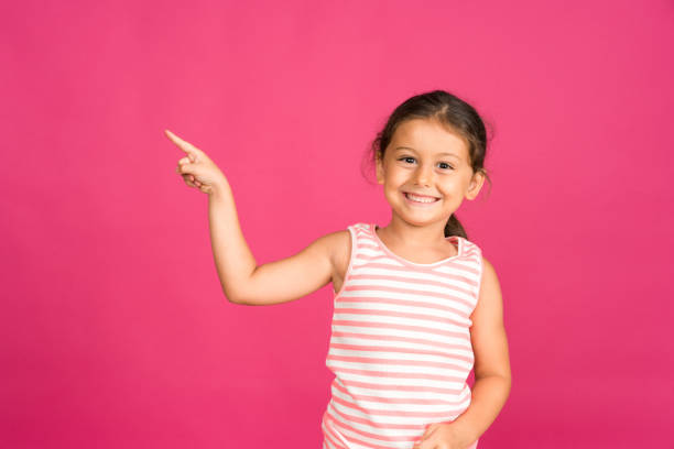 Cute little girl with a big smile, pointing to the side stock photo