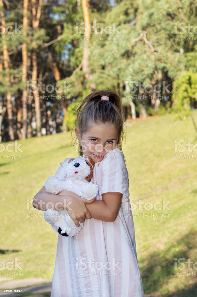 Cute little girl with a toy in the city park stock photo