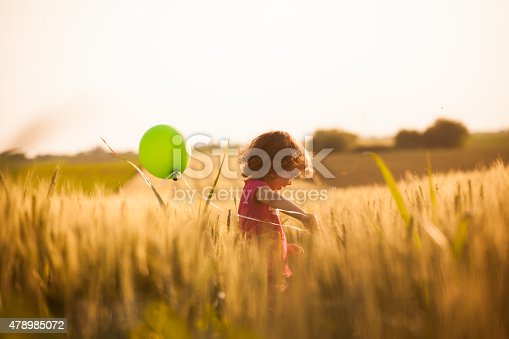 Cute little girl holding balloons and running through field