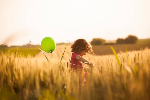 niedliche kleine mädchen mit luftballons im feld - weizen fotos stock-fotos und bilder