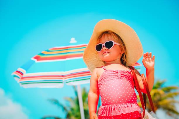 niedliche kleine mädchen mit big-bag am strand - sonnenbrille kleinkind stock-fotos und bilder