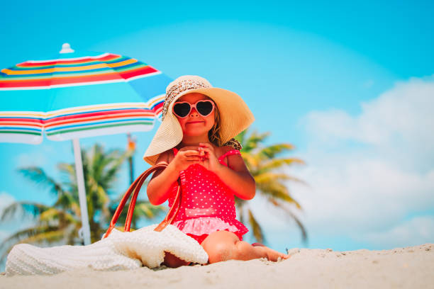 cute little girl with big hat and bag on beach stock photo
