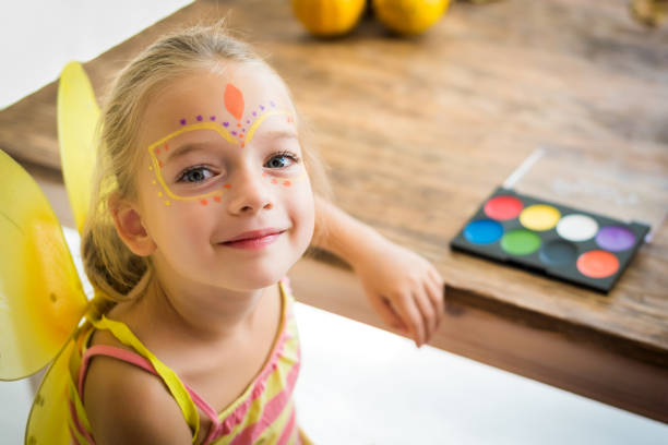 cute little girl with face paint sitting at a table, looking at camera smiling. halloween party or carnival family lifestyle background. face painting and dressing up. - school fete stock photos and pictures