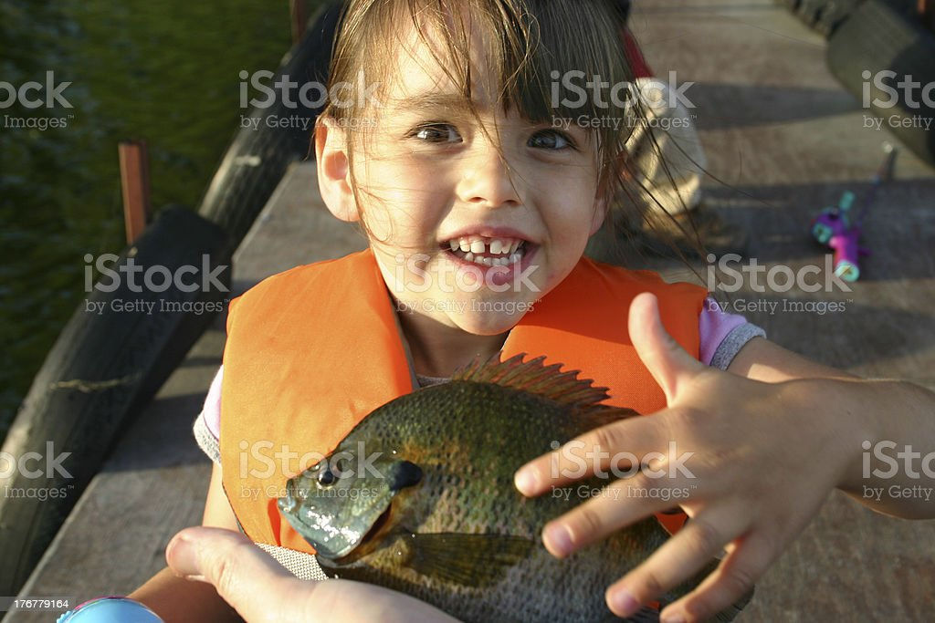 Cute little girl with first fish stock photo