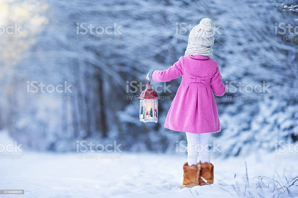 Cute little girl with flashlight having fun in winter day stock photo